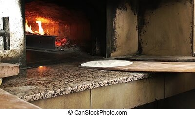 Adding Turkish Pizza to oven