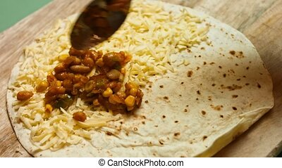 Adding vegetables to flour tortilla filled with grated cheese. Process of making mexican quesadillas with cheese and vegetables. Artistic shooting.