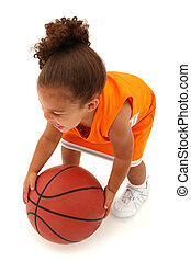 Adorable toddler girl child in orange sport uniform chasing basketball over white background.