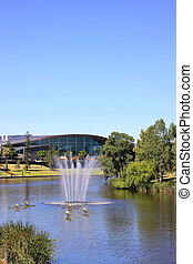 Adelaide Convention Centre along the banks of the River Torrens Lake, with a water fountain and 'paper boats' sculpture in the foreground. Adelaide, Australia