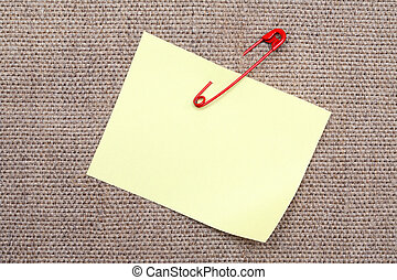 Blank yellow adhesive note attached with red safety pin to canvas background