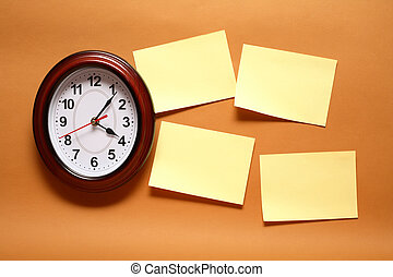 Few yellow blank adhesive notes hanging on the wall near clock