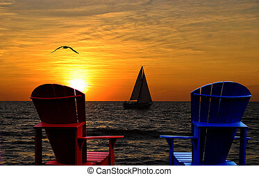 Pair of Adirondack chairs with Lake Michigan sunset and sailboat.
