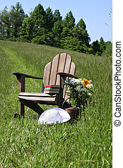 Adirondack chair with flowers and sunhat in a field of tall...