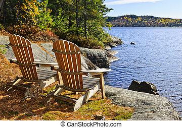 Adirondack chairs at lake shore - Adirondack chairs at shore...