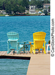 adirondack chairs on a dock on a summer day