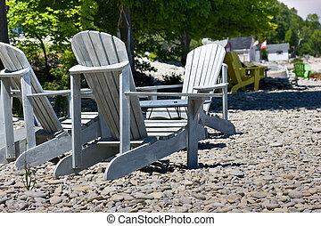 Adirondack chairs on rocky beach