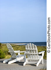 Adirondack chairs overlooking beach.