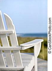 Adirondack chairs pointing toward ocean.