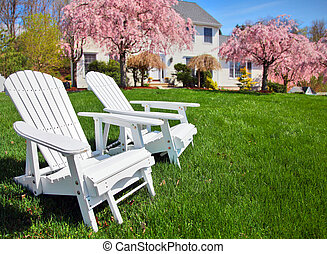 Adirondack chairs sitting on grass in front of generic...