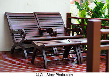 Adirondack wooden chairs on a patio in the garden.