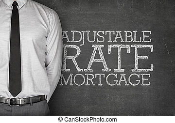 Adjustable rate mortgage text on blackboard with businessman...