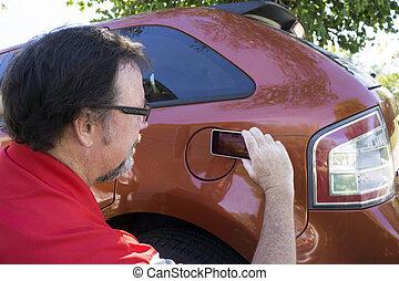 Adjuster Taking Photos Of Damage To Vehicle