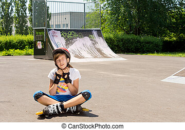 Young girl adjusts her protective head ware before continuing to practice rollerblading