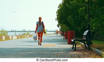 ADLER. RUSSIA - CIRCA AUG 2016: A female tourist is walking on the waterfront area of the resort town