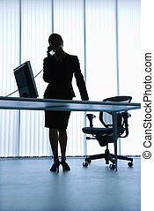 Silhouette of Caucasian businesswoman standing at computer desk on telephone.