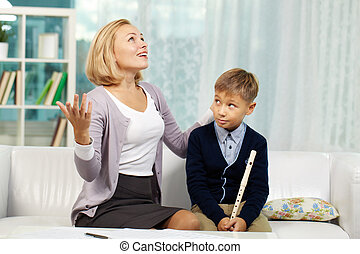 Portrait of pupil with the flute looking at his tutor speaking about music with admiration