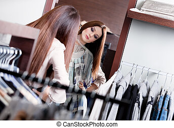 Admiring herself at the mirror while trying on a dress