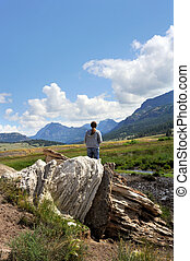 Female visitor to Yellowstone National Park, stands next to Soda Butte, a dormant hot springs, and admires Lamar Valley.