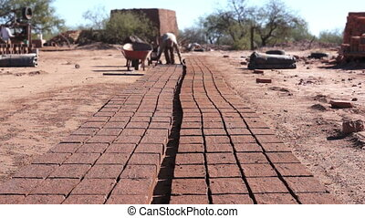 Adobe Brick Mud Loading Dolly - Long, dolly shot of a guy...