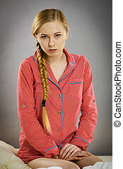 Sad young teenager woman sitting on bed
