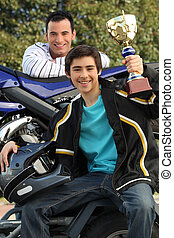 Adolescent boy holding up a trophy