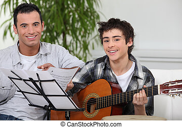 Adolescent boy learning to play the guitar