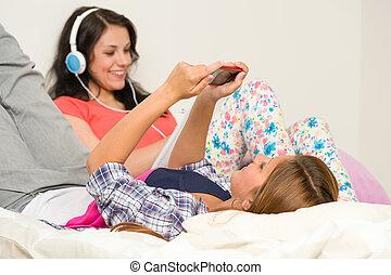 adolescent, délassant, vérification, filles, lit, téléphone