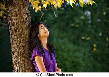 adolescent, feuilles automne, arbre, haut, regarder, penchant, girl