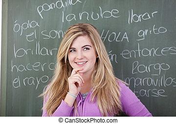 adolescent, tableau noir, écrit, contre, main, pensif, menton, mots, espagnol, girl