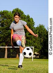 adolescente, bola, chutando, campo, menina, futebol