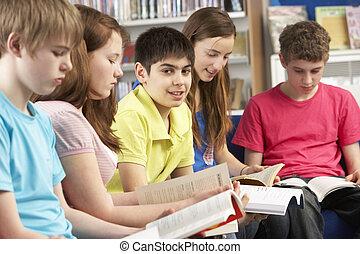 adolescente, estudantes, em, biblioteca, leitura, livros