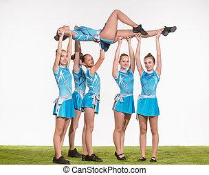 adolescente, grupo, cheerleaders, posar, estudio, blanco