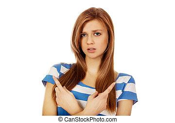 adolescente, mulher aponta, dois, confundido, direções, diferente