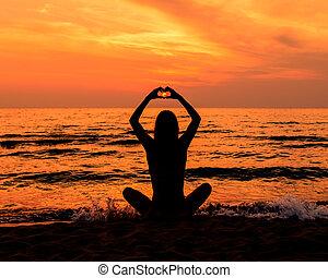 adolescente niña, en, un, vestido, con, pelo largo, en la playa, en, silueta, durante, ocaso, elaboración, un, corazón, con, ella, manos