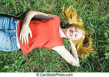 adolescente, niña, estar tendido en la hierba