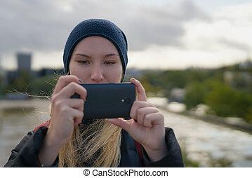 adolescente niña, tomar las fotos, con, smartphone, en la ciudad
