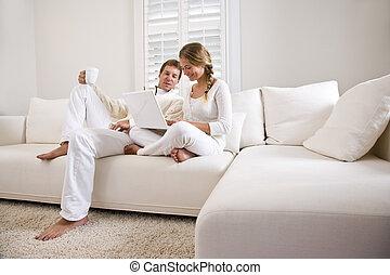 adolescente, padre, figlia, divano, vivente, usando, stanza, laptop, bianco