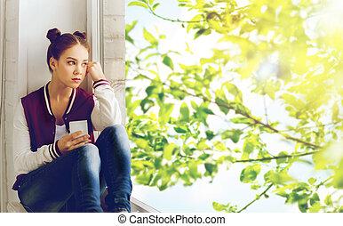 adolescente, smartphone, niña, alféizar, sentado