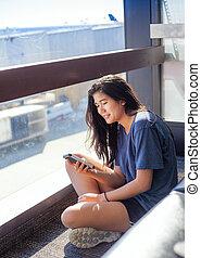 adolescente, smartphone, sentando, chão, olhar, aeroporto, menina