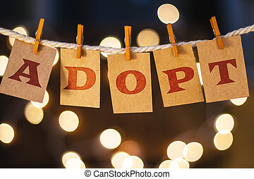 The word ADOPT printed on clothespin clipped cards in front of defocused glowing lights.