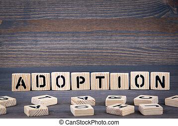 Adoption word written on wood block. Dark wood background with texture