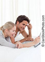 adorável, par, olhar, seu, laptop, cama