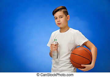 Adorable 11 year old boy child with basketball ball