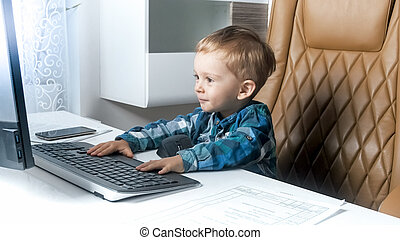 Adorable 2 years old toddler boy using computer in office. Concept of smart children
