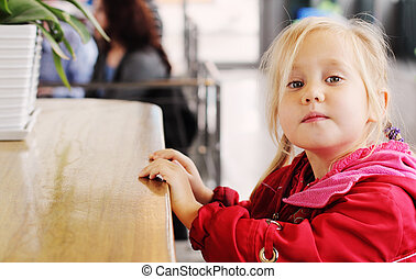 Adorable 4 years old girl sitting in cafe