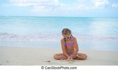 Adorable active little girl on a snow-white sandy beach
