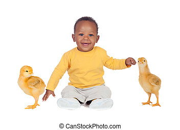 Adorable african baby sitting wit two little yellow chickens