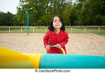 Adorable asian girl on a playground