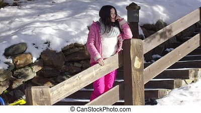 Adorable asian girl standing on wooden stairs